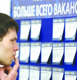 A man reads job offers posted at a job fair in Moscow